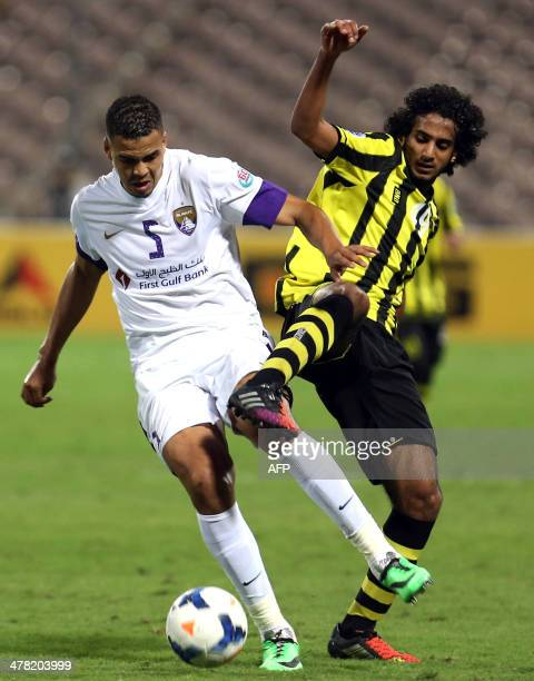 Saudi Arbia's AlIttihad Abdullrahman alGhamdi fights for the ball with UAE's AlAin Ismail Ahmed during their AFC Champions League football match in...