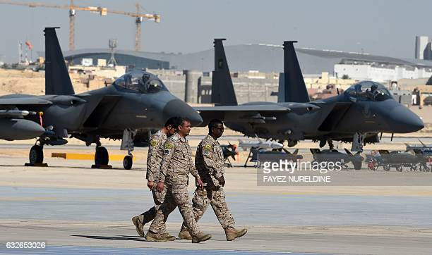 Saudi army officers walk past F15 fighter jets GBU bombs and missiles displayed during a ceremony marking the 50th anniversary of the creation of the...