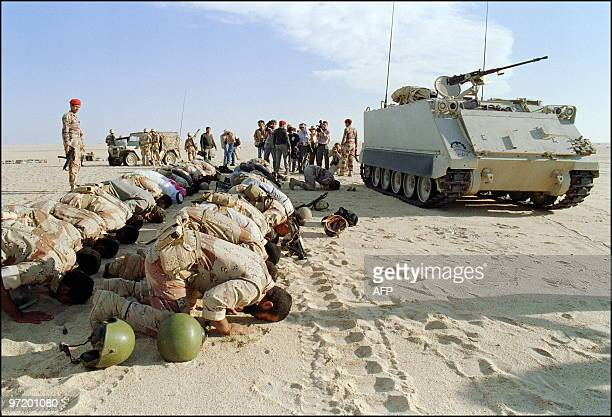 Saudi army soldiers pause during maneuvers somewhere in Saudi desert 02 December 1990 bowing to pray as part of Moslem rituals At right M113 USmade...