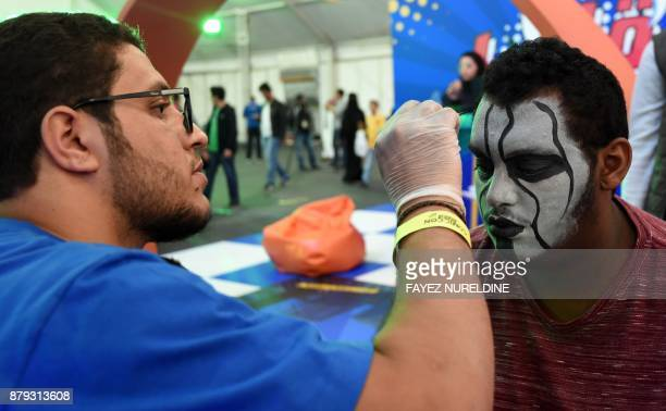 A Saudi artist applies facepaint to a cosplayer as they attend the first ever ComicCon Arabia event held in the capital Riyadh on November 25 2017 /...