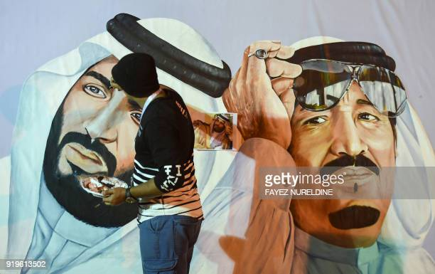 Saudi artists paint a mural portrait of King Salman bin Abdulaziz and his son Crown Prince Mohammed bin Salman during the 32nd Janadriyah Culture and...