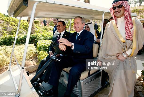 Saudi billionaire Price Walid bin Talal walks along as US President George W Bush drives a golf cart to the event site with Egyptian President Hosni...