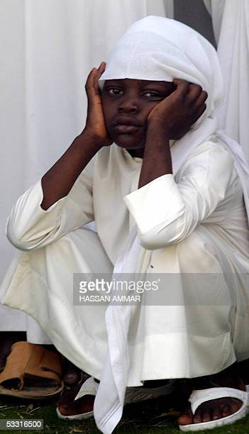 Saudi boy sits outside the Imam Turki bin Abdullah mosque during the funeral of late King Fahd in Riyadh 02 August 2005 Fahd died yesterday after 23...
