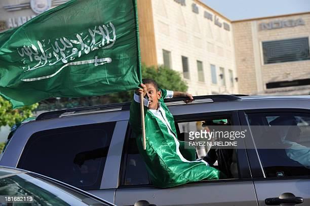 A Saudi boy waves the national flag during celebrations marking the 83rd Saudi Arabian National Day in the desert kingdom's capital Riyadh on...