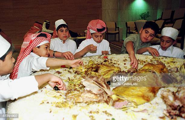 Saudi boys eat the traditional Eid alFitr dish stuffed lamb with saffron rice nuts and spices after prayers at Riyadh's Grand mosque 16 December 2001...