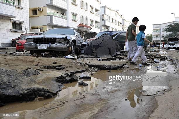 Saudi boys walk past damaged vehicles amd torn up tarmac following heavy rains and floods in the city of Jeddah on January 27 as Saudi emergency...