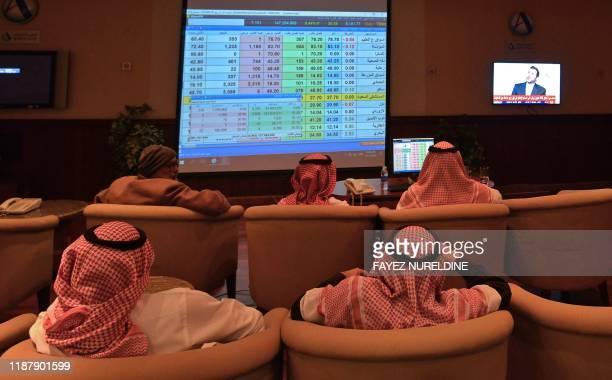 Saudi brokers monitor the stock market at the Arab National Bank in the Saudi capital Riyadh on December 11, 2019. - Saudi Aramco's shares soared on...