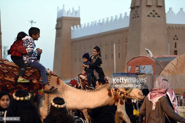 Saudi children ride camels during the Janadriyah festival of Heritage and Culture held in the Saudi village of AlThamama 50 kilometres north of the...