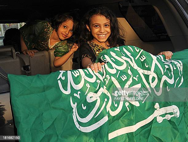 Saudi children sitting in the back of a car display a national flag during celebrations marking the 83rd Saudi Arabian National Day in the desert...