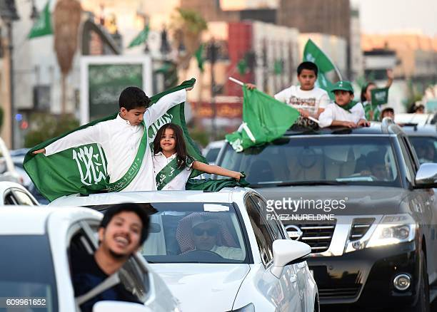 Saudi children wave their national flag as cars drive along the street during celebrations marking the 86th Saudi Arabian National Day in the desert...