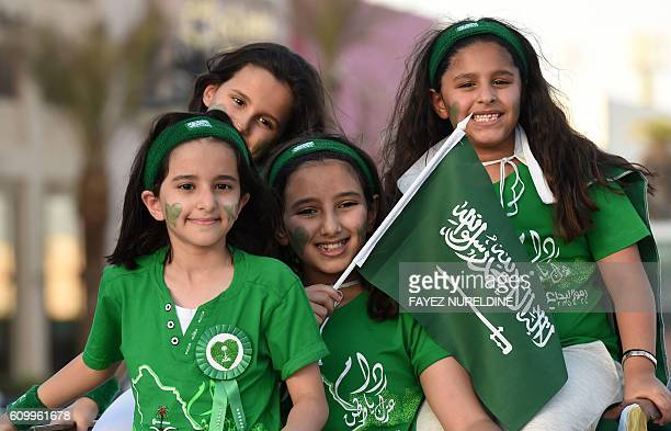 Saudi children wave their national flag during celebrations marking the 86th Saudi Arabian National Day in the desert kingdom's capital Riyadh on...