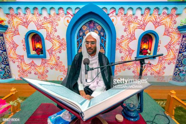 A Saudi cleric recites from a copy of the Koran Islam's holy book at a mosque on the first day of the holy fasting month of Ramadan in the coastal...