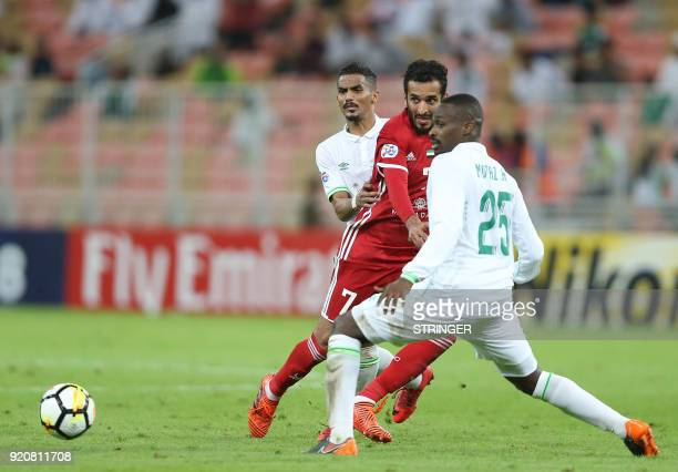 Saudi club AlAhli's Motaz Hawsawi vies for the ball against UAE's AlJazira's Ali Mabkhout during their AFC Champions League match between alAhli...