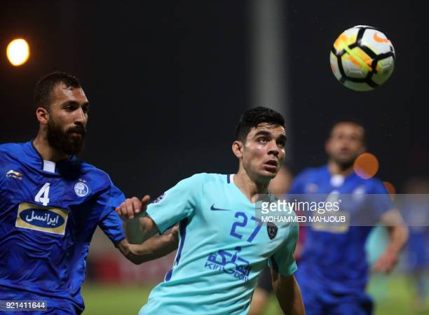 Saudi club AlHilal's Achraf Bencharki fights for the ball with Roozbeh Cheshmi of Iranian club Esteghlal during their Asian Champions League football...