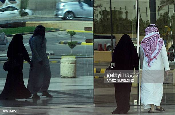 A Saudi couple enters a shopping mall in the capital Riyadh on October 26 2013 as Saudi women scrapped a 'drivein' and opted for an openended...