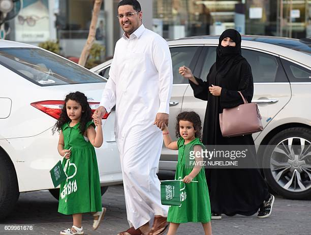 A Saudi couple walk with their children holding their national flag during celebrations marking the 86th Saudi Arabian National Day in the desert...
