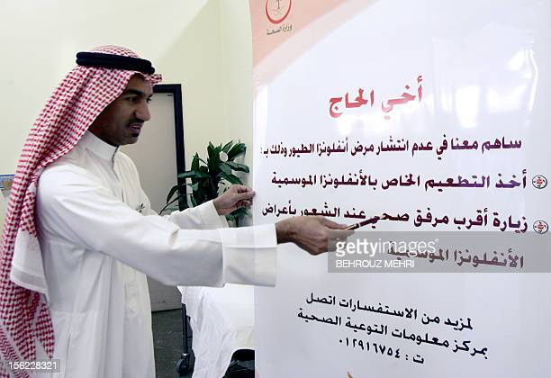 Saudi director of the health control centre at King Abdul Aziz airport doctor Mohammed alHarthi points to a health warning against avian flu and and...