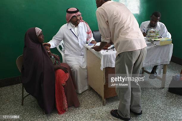 Saudi doctor from Physicians Across Continents speaks through a Somali translator after seeing a malnourished child at the Banadir hospital on August...