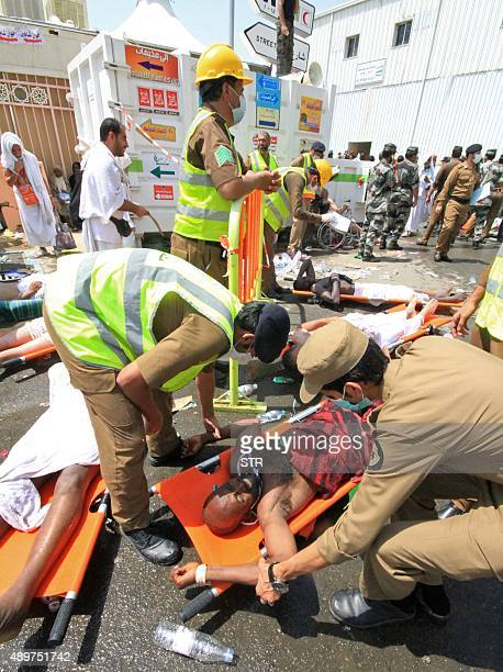 Saudi emergency personnel help a wounded person at the site where at least 450 were killed and hundreds wounded in a stampede in Mina near the holy...