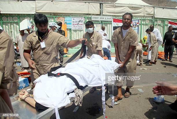 Saudi emergency personnel transport a body at the site where at least 450 were killed and hundreds wounded in a stampede in Mina near the holy city...