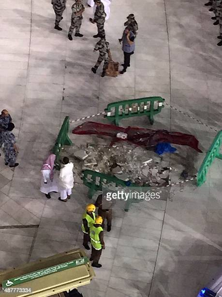 Saudi emergency teams gather inside the Grand Mosque of Saudi Arabia's holy Muslim city of Mecca next to a piece of a construction crane after it...