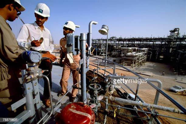 Saudi engineers stand on a storage tank at the Haradh Natural Gas And Oil Development Project part of a developed gas plant to deliver gas to the...