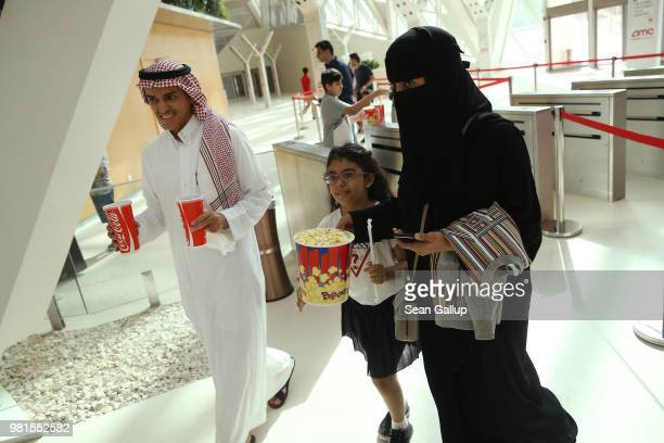 Saudi family carrying Cokes and popcorn arrives to watch 'The Incredibles 2' at the newlyopened AMC Cinema in the King Abdullah Financial District on...