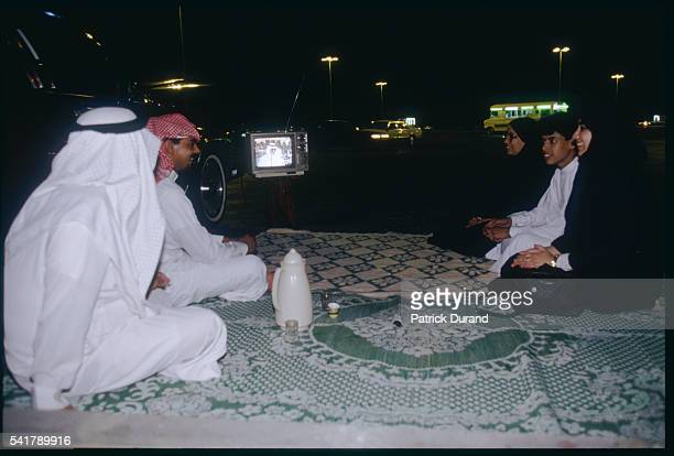 Saudi Family Watching Television near the Beach