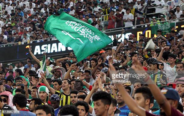 Saudi fans wave the national flag and chant during the 2018 World Cup qualifying football match between Saudi Arabia and United Arab Emirates at the...