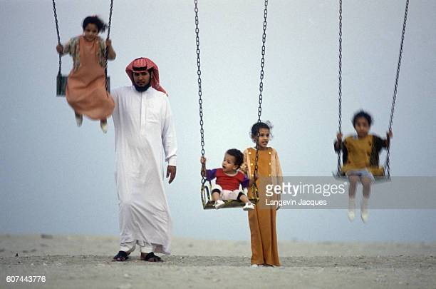 A Saudi father and his four children play on a swing set on a beach in Saudi Arabia There is a private beach for foreigners surrounded by a concrete...