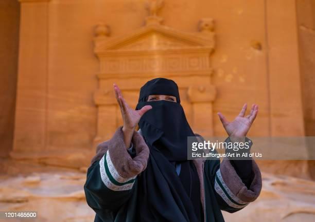 Saudi female guide in front of a tomb in al-Hijr archaeological site in Madain Saleh, Al Madinah Province, Alula, Saudi Arabia on December 27, 2019...