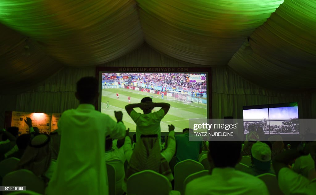 TOPSHOT - Saudi football fans cheer for their national team during their Russia 2018 World Cup Group A football match against Russia at a fan tent in the capital Riyadh on June 14, 2018.