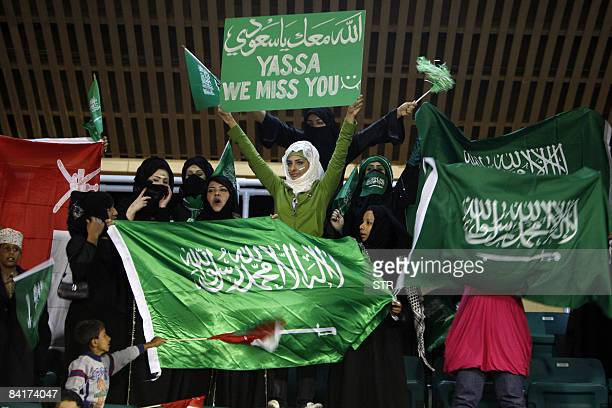 Saudi football fans hold national flags and banners as they cheer for their team before kickoff of their match against Qatar during the 19th Gulf Cup...