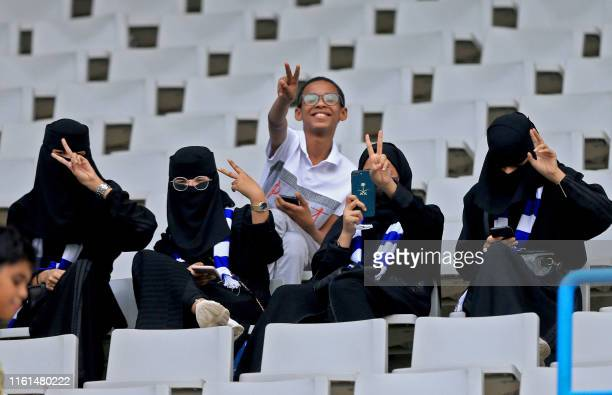 Saudi football fans, including women, flash the victory gesture as they wait for their team in the stands ahead of the AFC Champions League play-off...