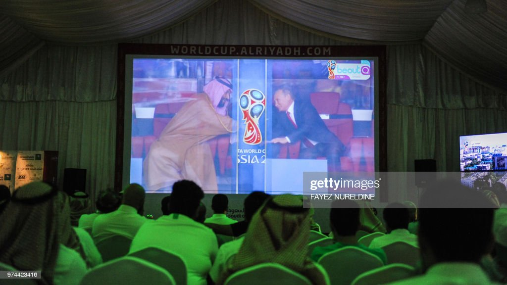 TOPSHOT - Saudi football fans watch the Russia 2018 World Cup Group A football match between Russia and Saudi Arabia at a fan tent in the capital Riyadh on June 14, 2018, as the screen shows Crown Prince Mohammed bin Salman (L) reaching out to Russian President Vladimir Putin (R).