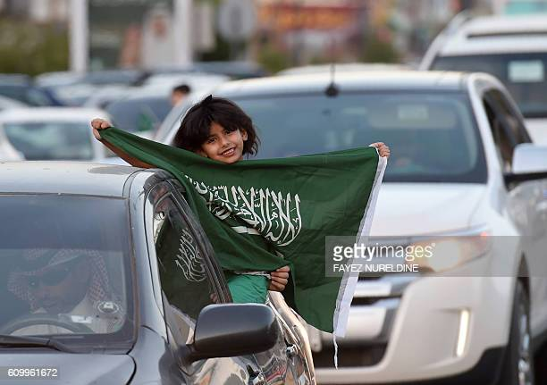 A Saudi girl holds her national flag during celebrations marking the 86th Saudi Arabian National Day in the desert kingdom's capital Riyadh on...