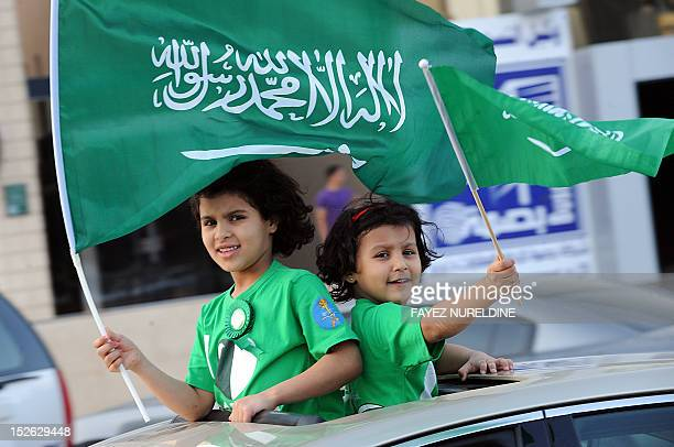 Saudi girls wave their national flag during celebrations marking the 82nd Saudi National Day in the desert kingdom's capital Riyadh on September 23...