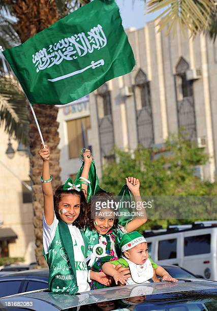 Saudi girls wave their national flag during celebrations marking the 83rd Saudi Arabian National Day in the desert kingdom's capital Riyadh on...