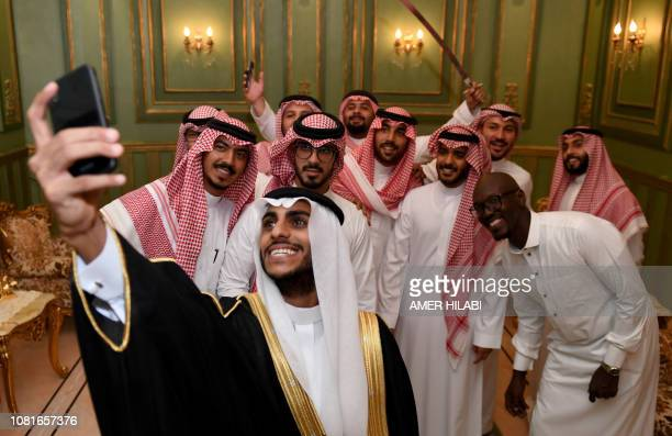 Saudi groom Basil Albani poses for a selfie with his friends during his wedding at his home in the Red Sea resort of Jeddah on September 6 2018 It...
