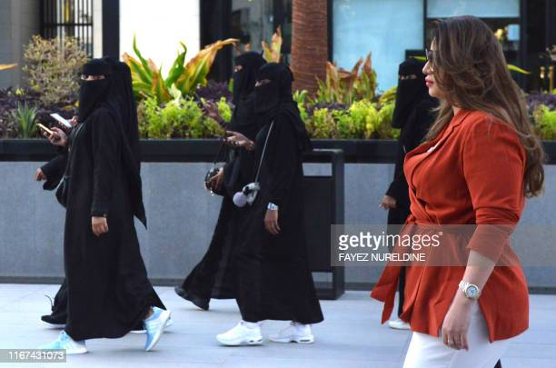 Saudi human resources professional Mashael al-Jaloud walks in western clothes past women wearing niqab, an Islamic dress-code for women, at a...