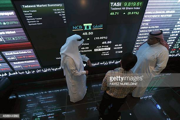Saudi investors monitor stocks at the newly opened exchange market department at the National Commercial Bank in Riyadh on November 12 2014 NCB...