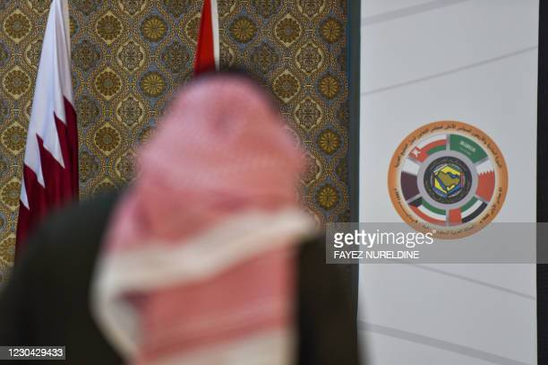 Saudi journalist is pictured in front of the logo of the Gulf Cooperation Council and the Qatari national flag at the media centre ahead of the 41st...