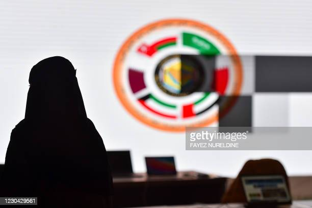 Saudi journalist is pictured in front of the logo of the Gulf Cooperation Council at the media centre ahead of the 41st summit in the city of al-Ula...