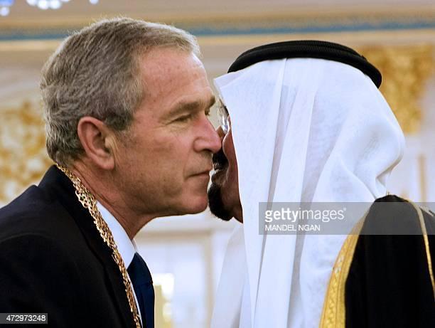 Saudi King Abdullah bin Abdul Aziz alSaud embraces US President George W Bush shake hands after presenting him with the King Abdul Aziz Order of...