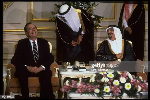 Saudi King Fahd sharing laugh w Pres Bush sitting mtg w Desert Shield Mideast gulf crisistouring Pres w translator hovering over them