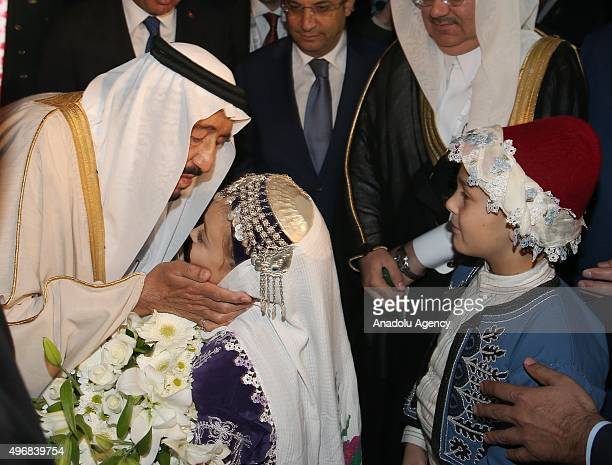 Saudi King Salman bin Abdul Aziz Al Saud kisses a little girl who presented flowers to him upon his arrival at the Antalya International Airport for...