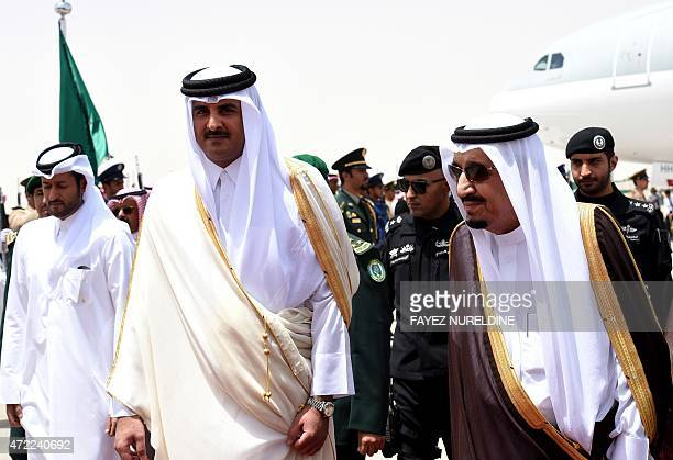Saudi King Salman bin Abdulaziz escorts Qatar's Emir Sheikh Tamim bin Hamad AlThani upon his arrival in Riyadh to attend the Gulf Cooperation Council...