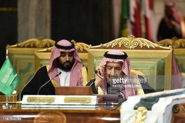Saudi King Salman bin Abdulaziz , flanked by his son Crown Prince Mohammed bin Salman , puts on his spectacles as he prepares to read a document...