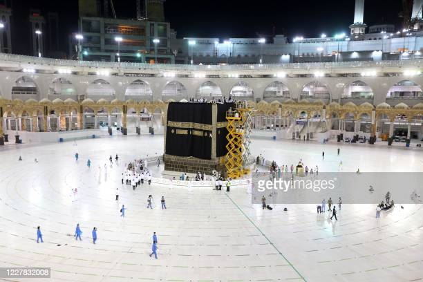 Saudi labourers put the new Kiswa the protective cover that engulfs the Kaaba made from black silk and gold thread and embroidered with Koran verses...