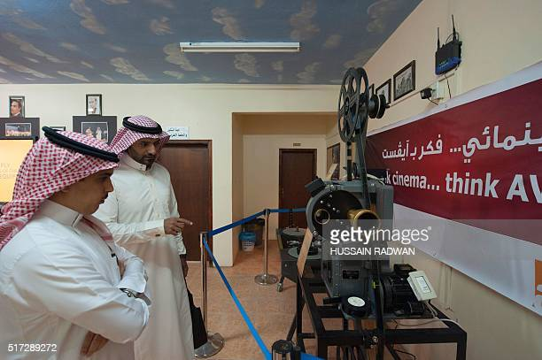 Saudi look at an ancient projector displayed during the opening ceremony of the film festival on March 24, 2016 at the Saudi Cultural Center in...